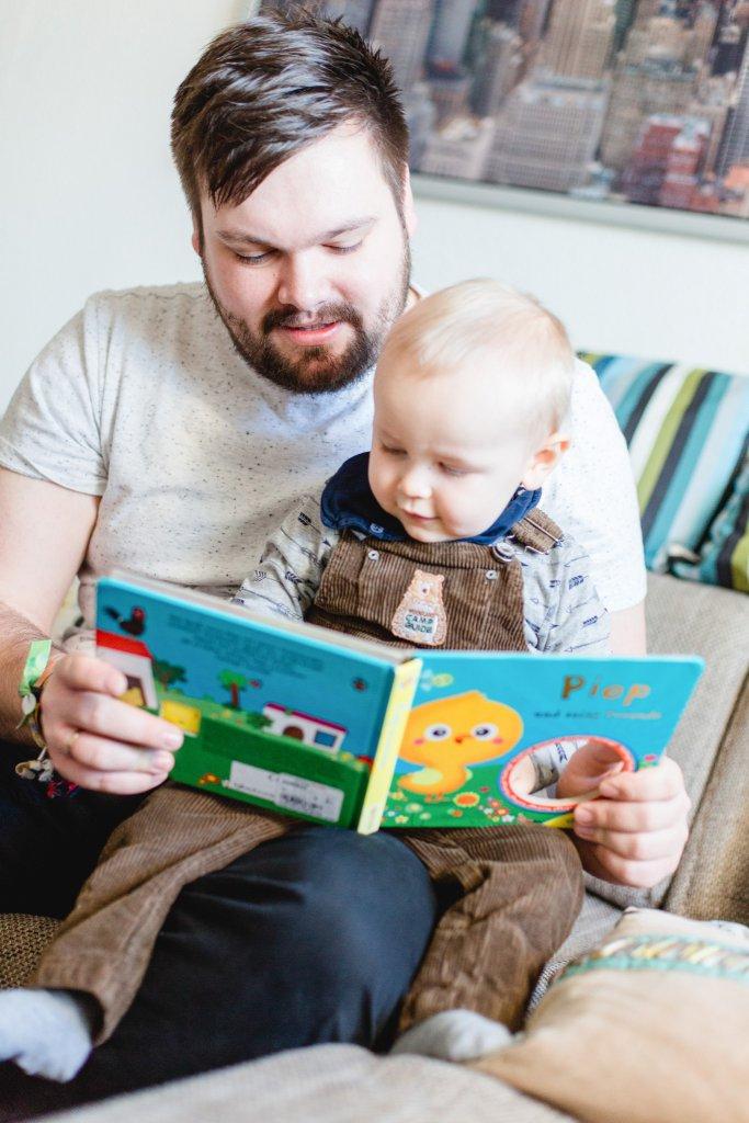 Foto von einem Papa, der mit seinem Sohn ein Buch anschaut.