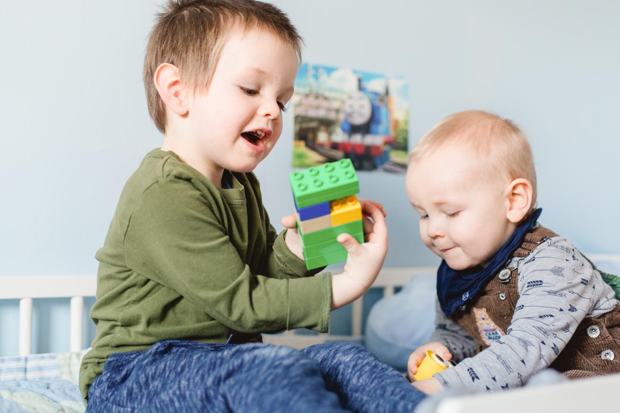 Geschwister beim Spielen im Bett des großen Bruder.