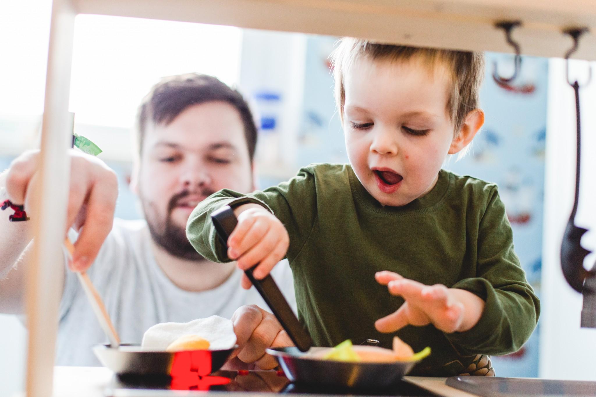 Foto eines Kindes beim Kochen an seiner Kinderküche.
