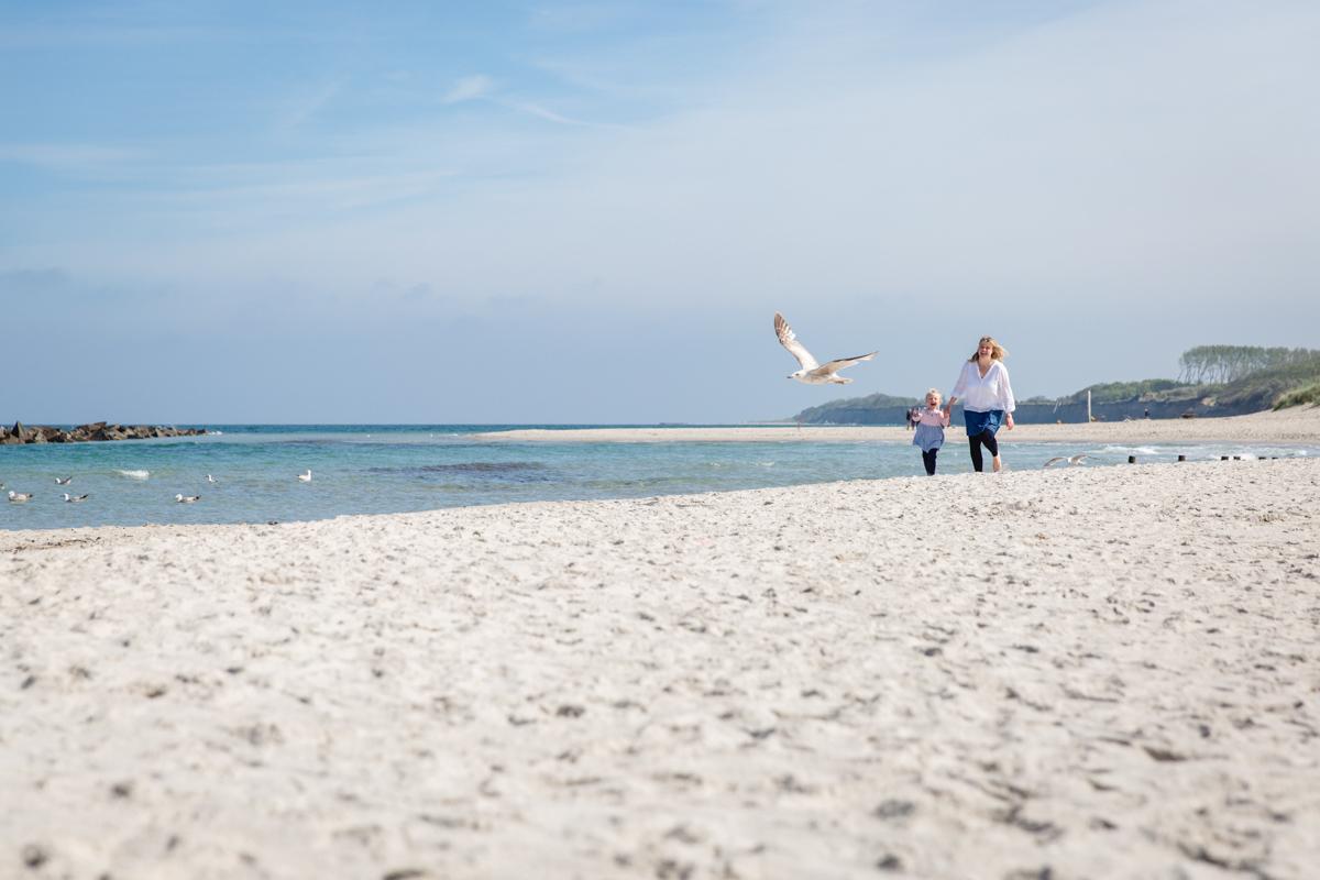 Tochter und Mama auf Möwenjagd am Strand.