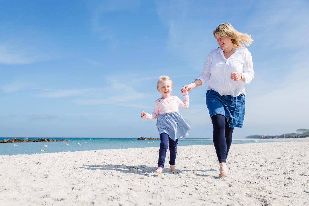 Tochter flitzt mit Mama an der Hand am Strand entlang.